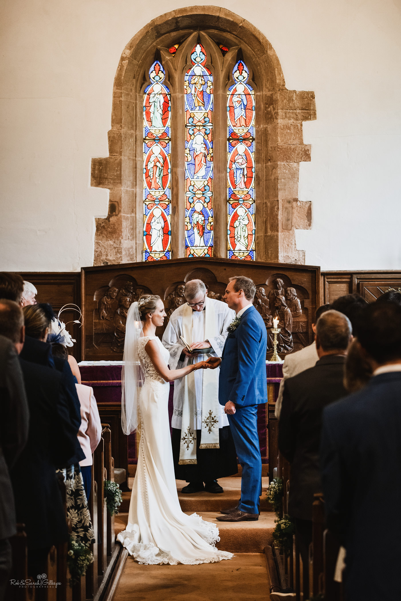Bride and groom exchange rings during wedding at St Kenelm's church