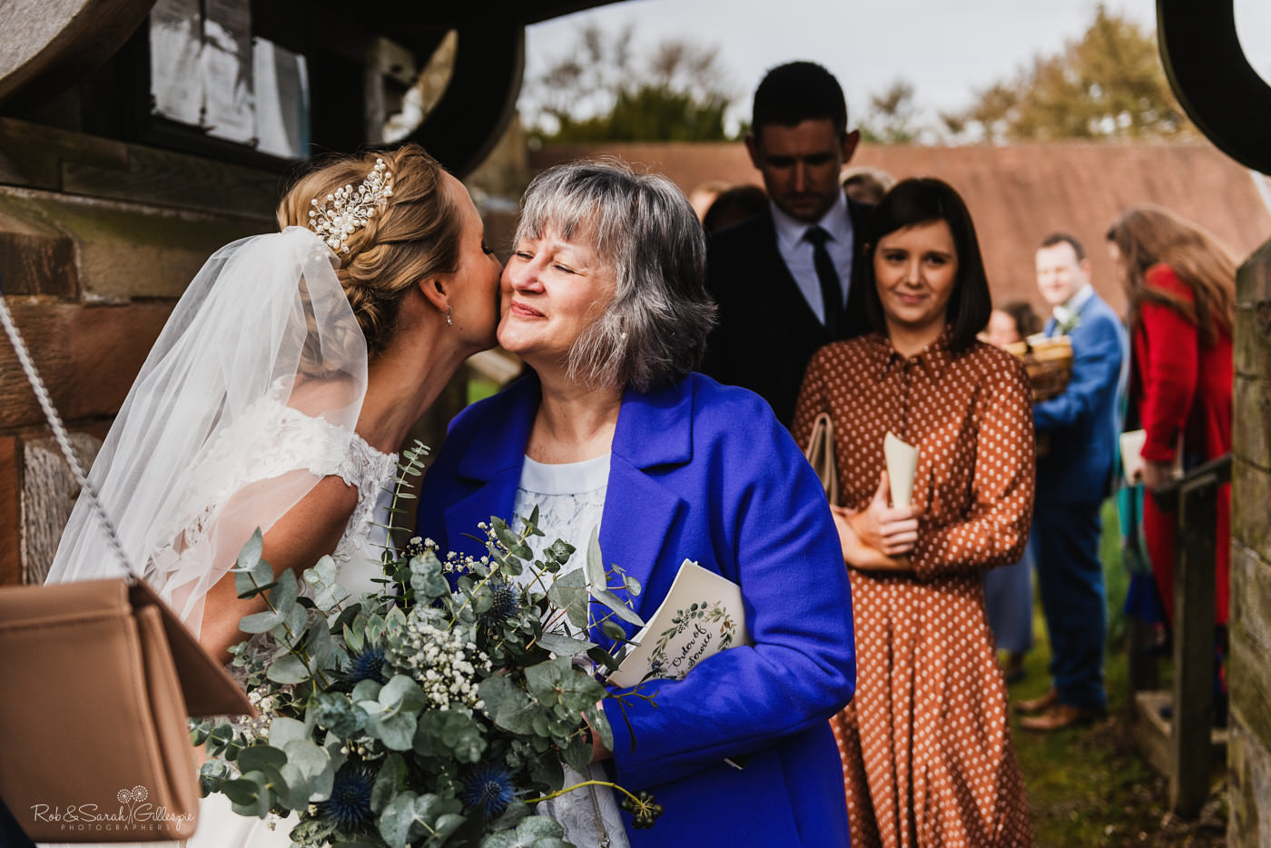 Wedding guests congratulate bride and groom at St Kenelm's church in Worcestershire