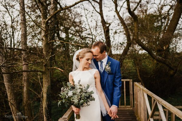 Bride and groom on wooden bridge at Swallows Nest Barn