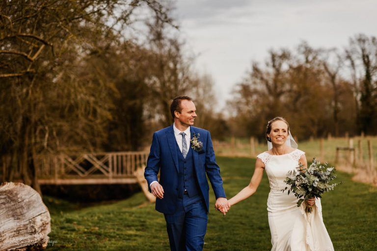 Bride and groom walking together through grounds at Swallows Nest Barn