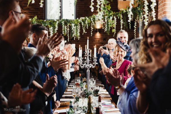 Wedding guests clap as bride and groom enter