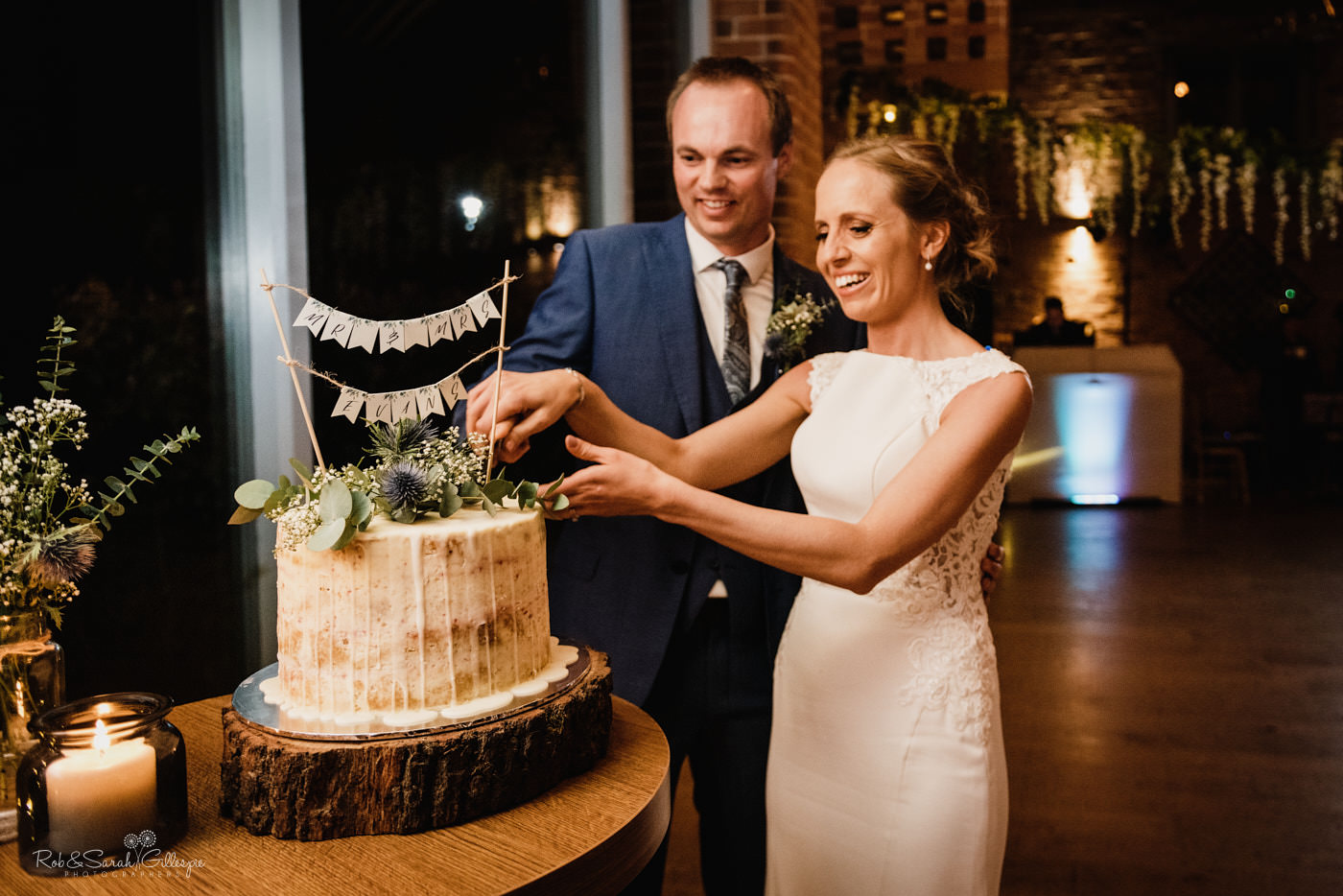 Bride and groom cut wedding cake at Swallows Nest Barn