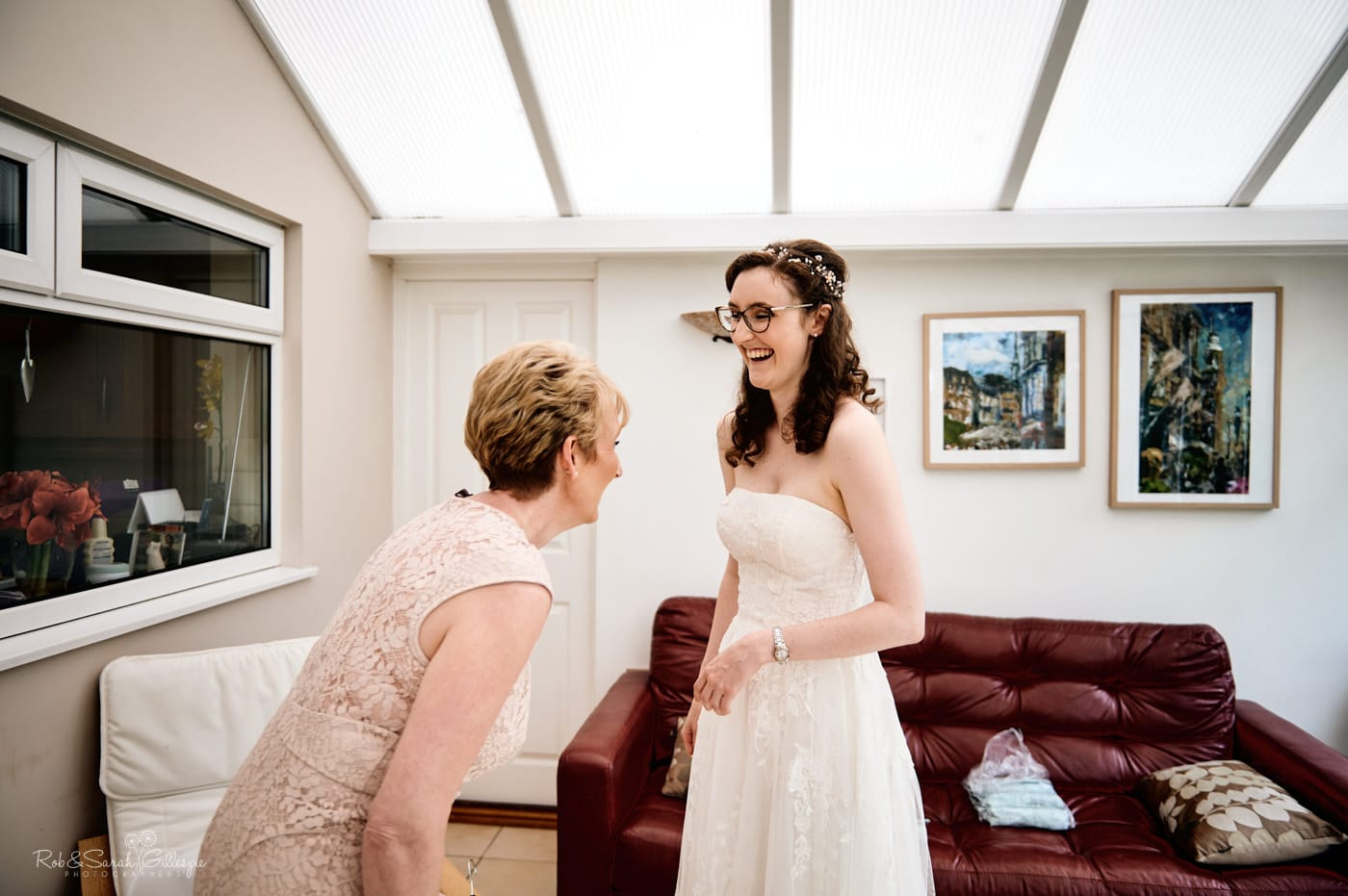 Bride and mum laughing as they get ready for wedding