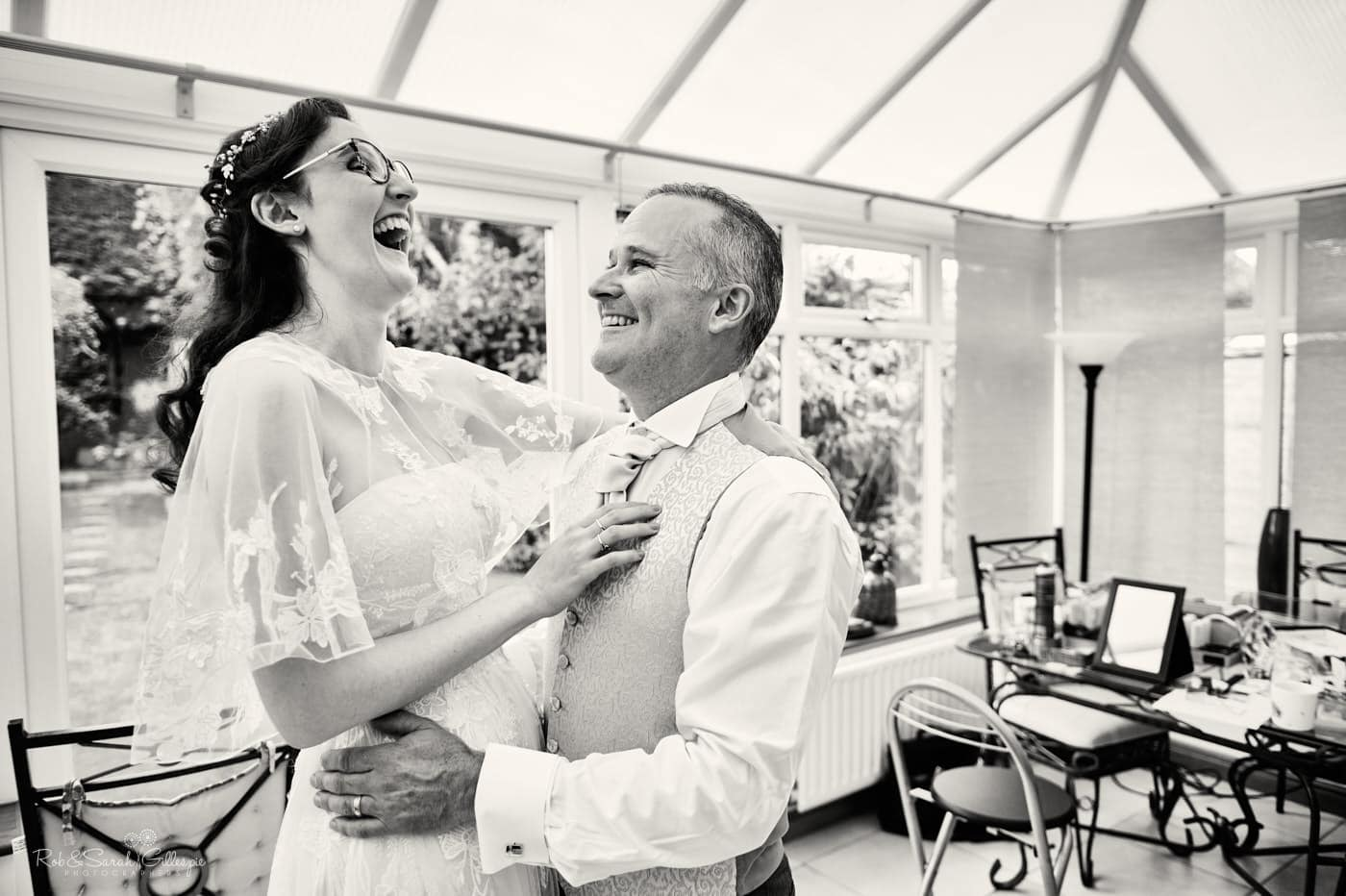 Bride laughing with dad as she prepares for wedding