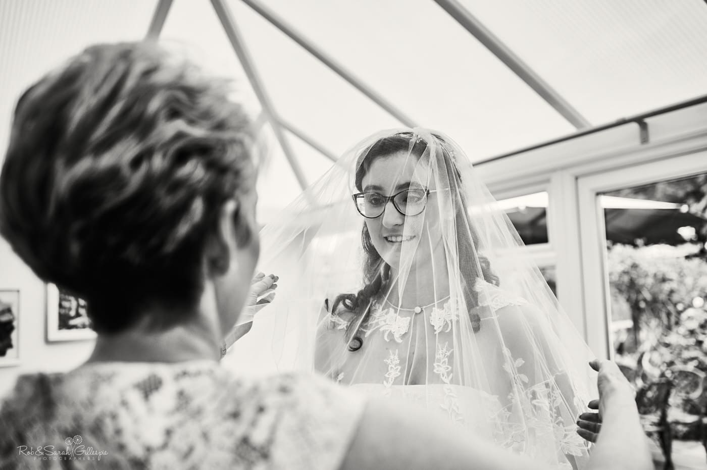 Bride has veil adjusted by mum before wedding