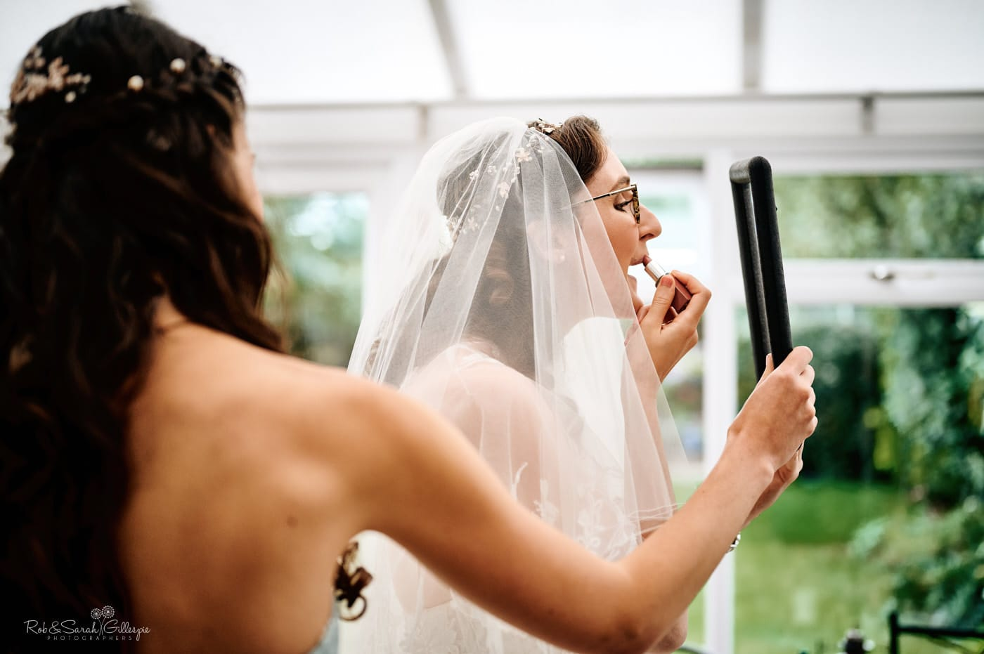 Bride applies lipstick for wedding