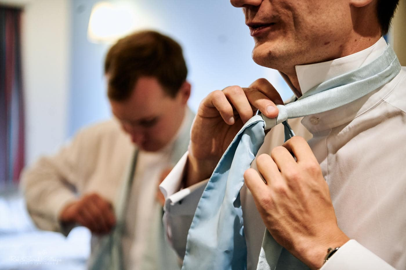 Groom adjusts tie as he gets ready for wedding