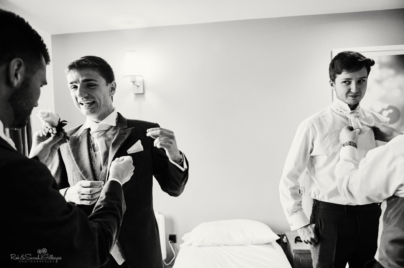 Groomsmen prepare for wedding in hotel room