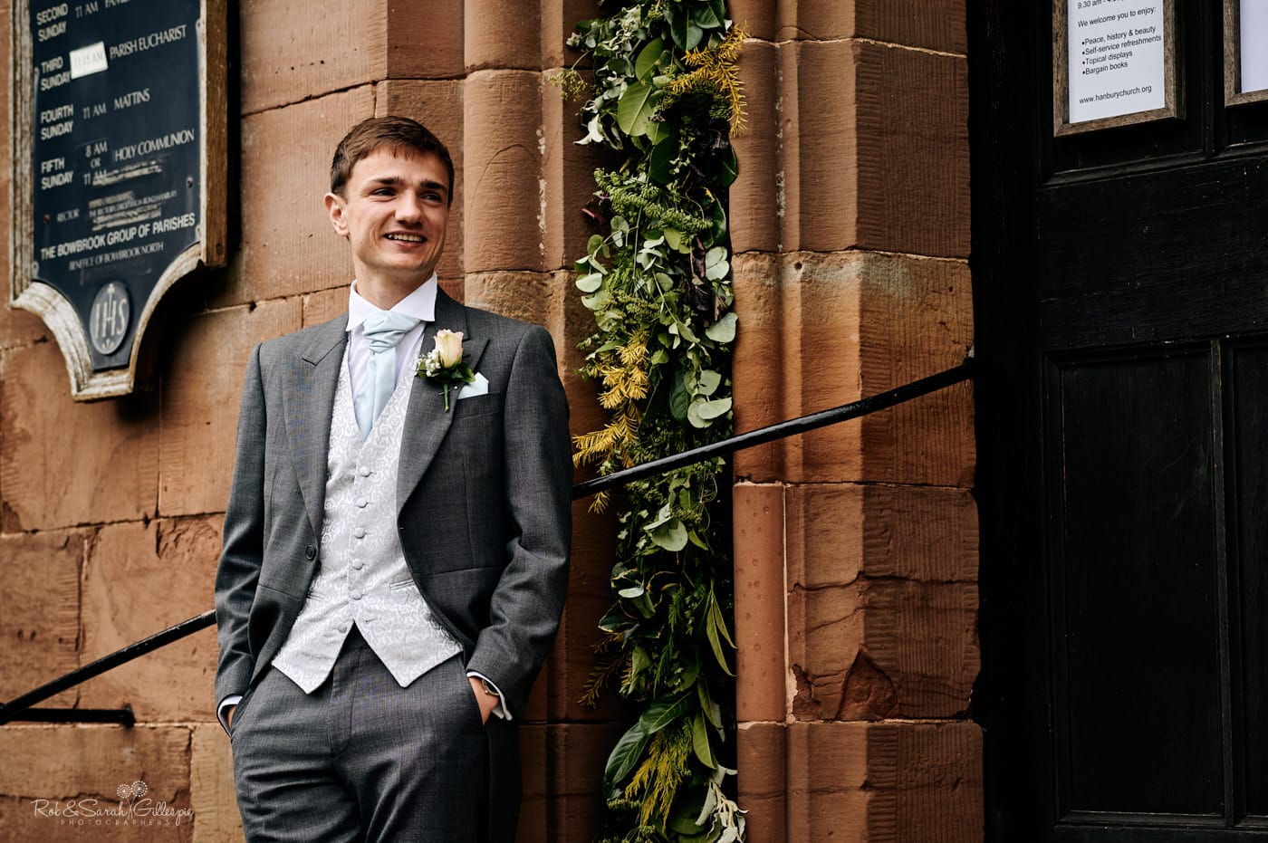 Groom standing on steps of Hanbury Church in Worcestershire