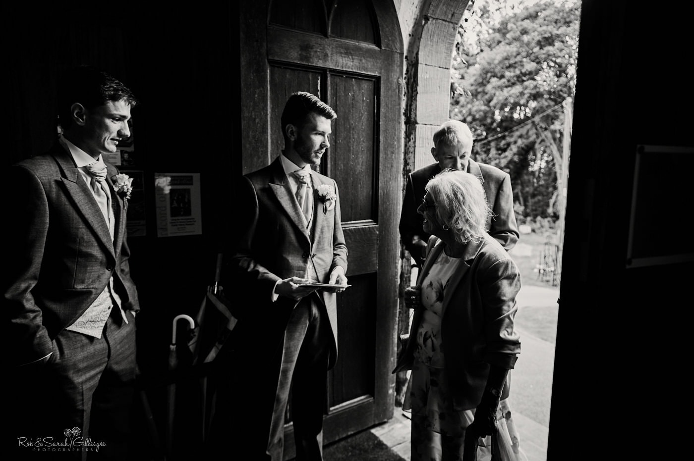Groomsmen greet wedding guests at Hanbury Church