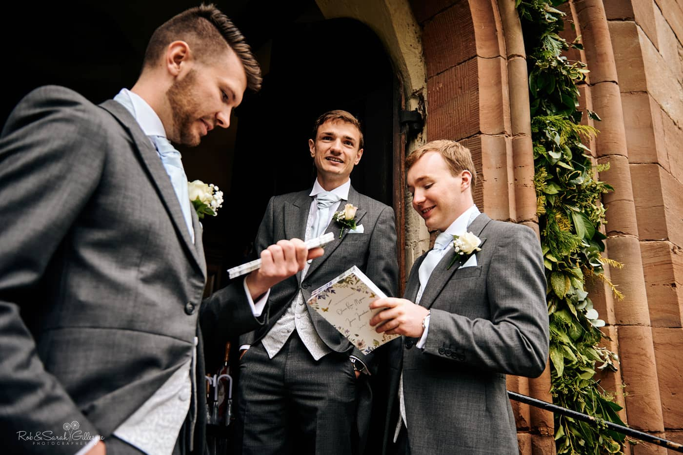 Groom and groomsmen wait for wedding guests at Hanbury Church