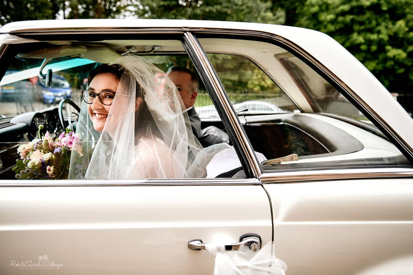 Bride smiling at bridesmaids as she arrives for wedding at Hanbury Church