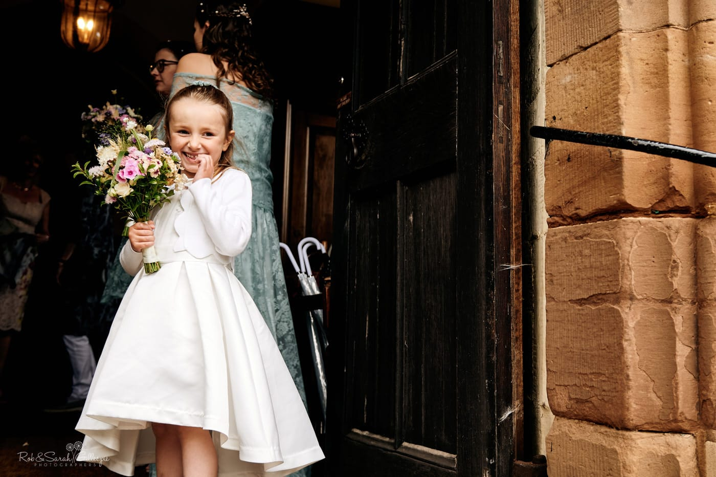 Flowergirl smiling back at bride at Hanbury Church