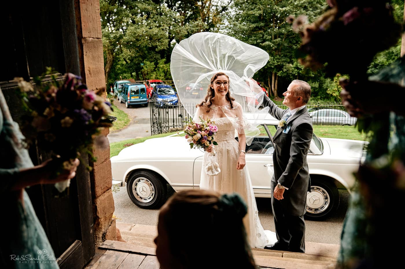 Bride's veil billows in the wind at Hanbury Church wedding