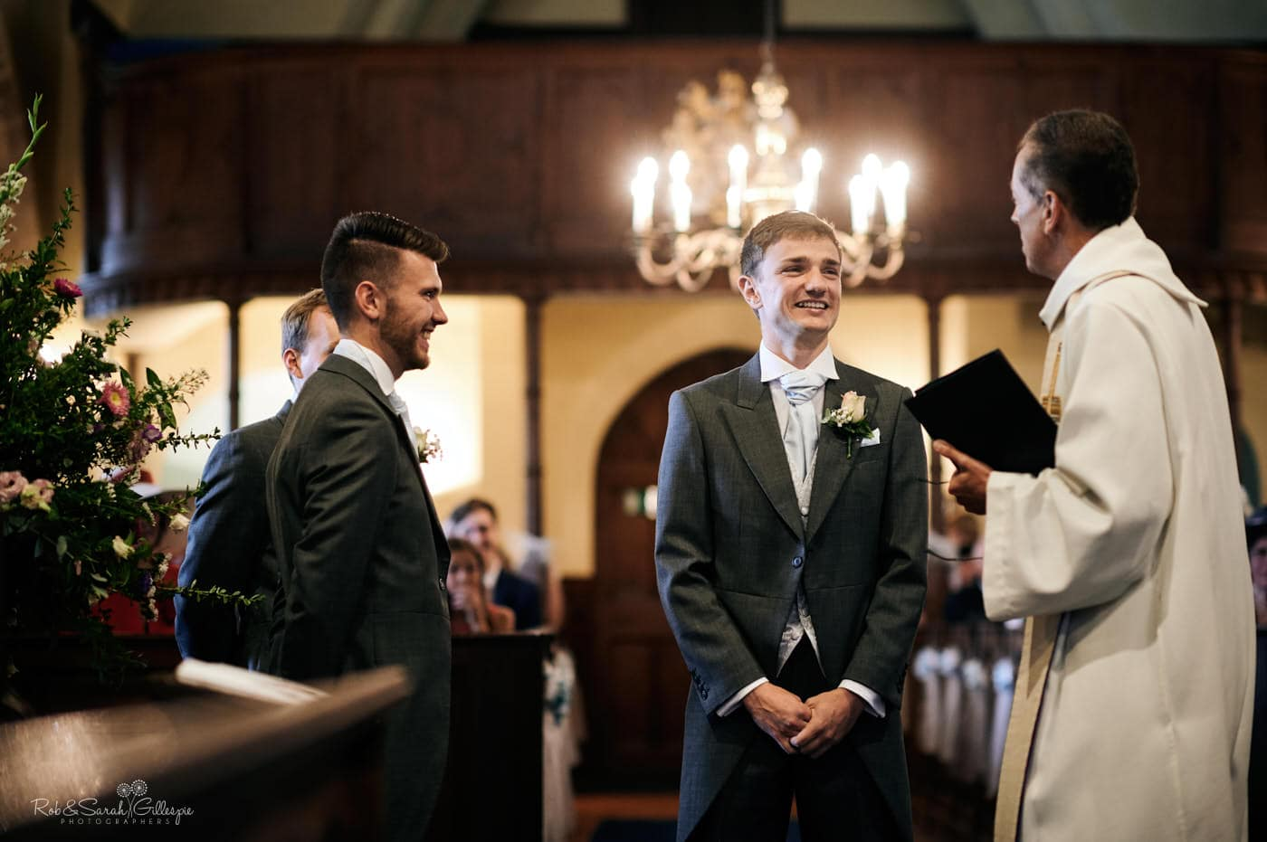 Groom talks to vicar before wedding at Hanbury Church in Worcestershire