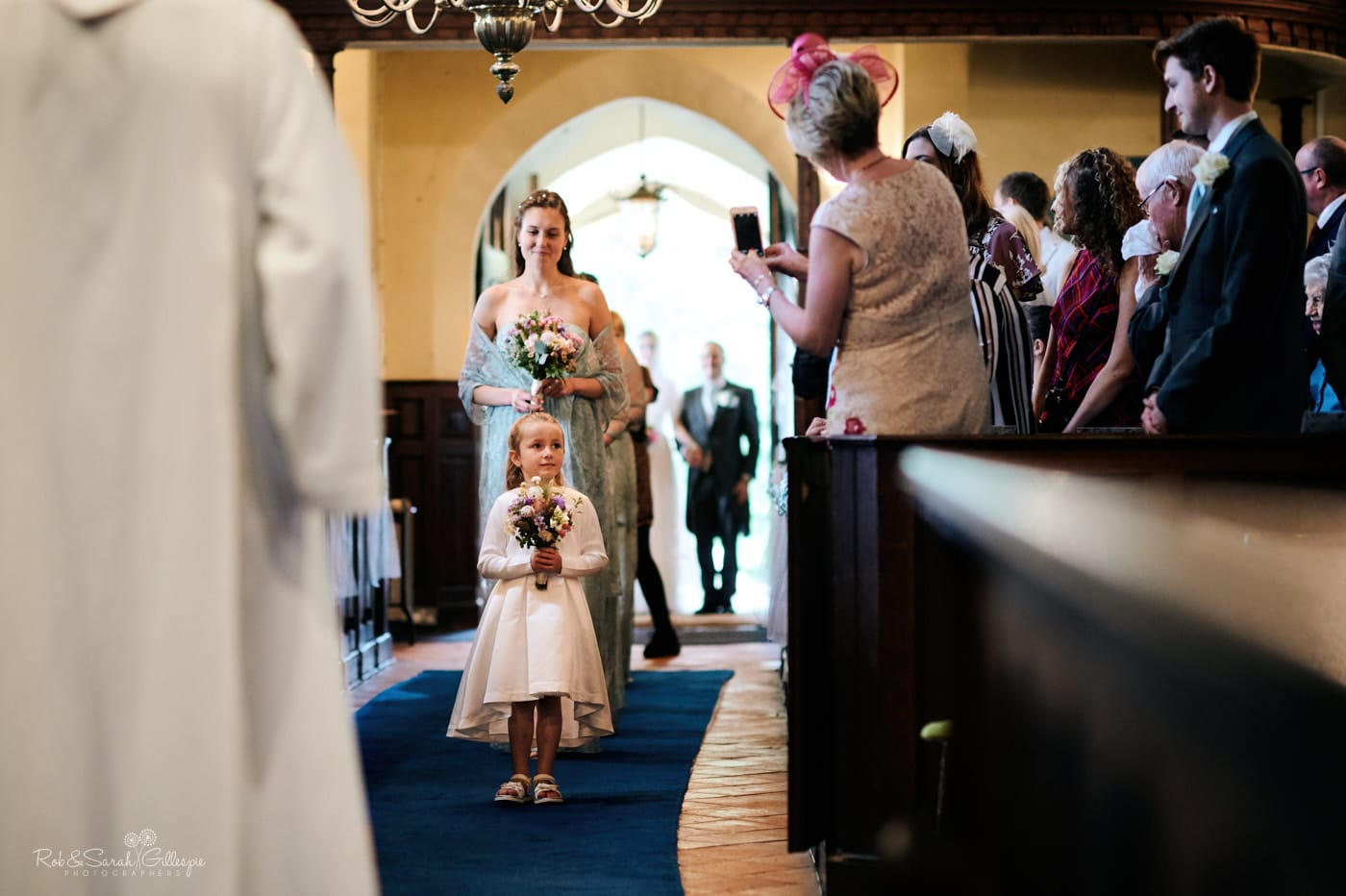 Flowergirl and bridesmaids enter church for wedding ceremony