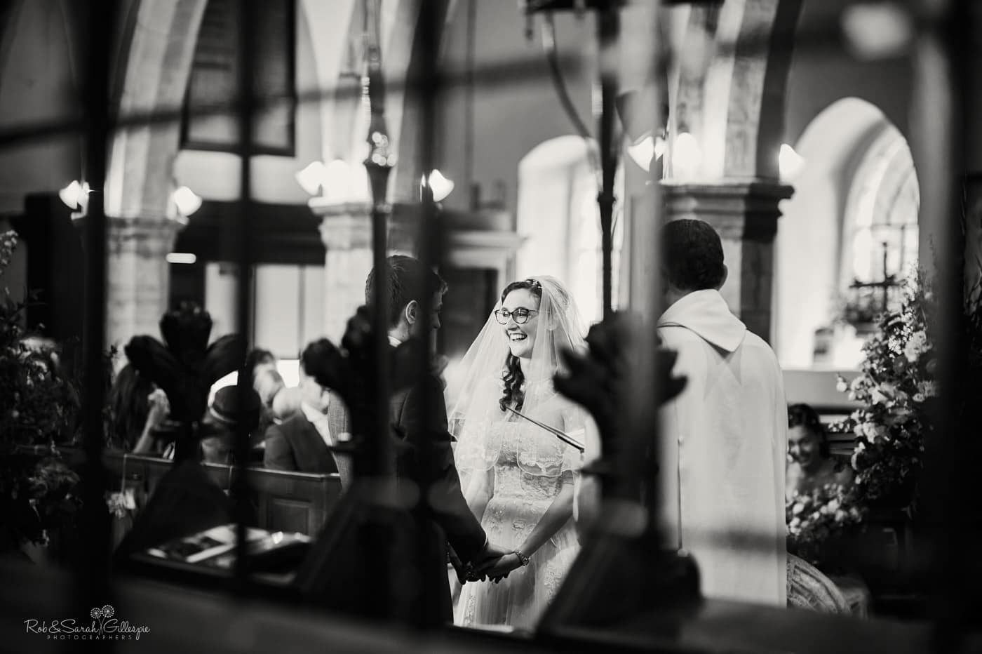 Bride laughing during wedding ceremony at Hanbury Church