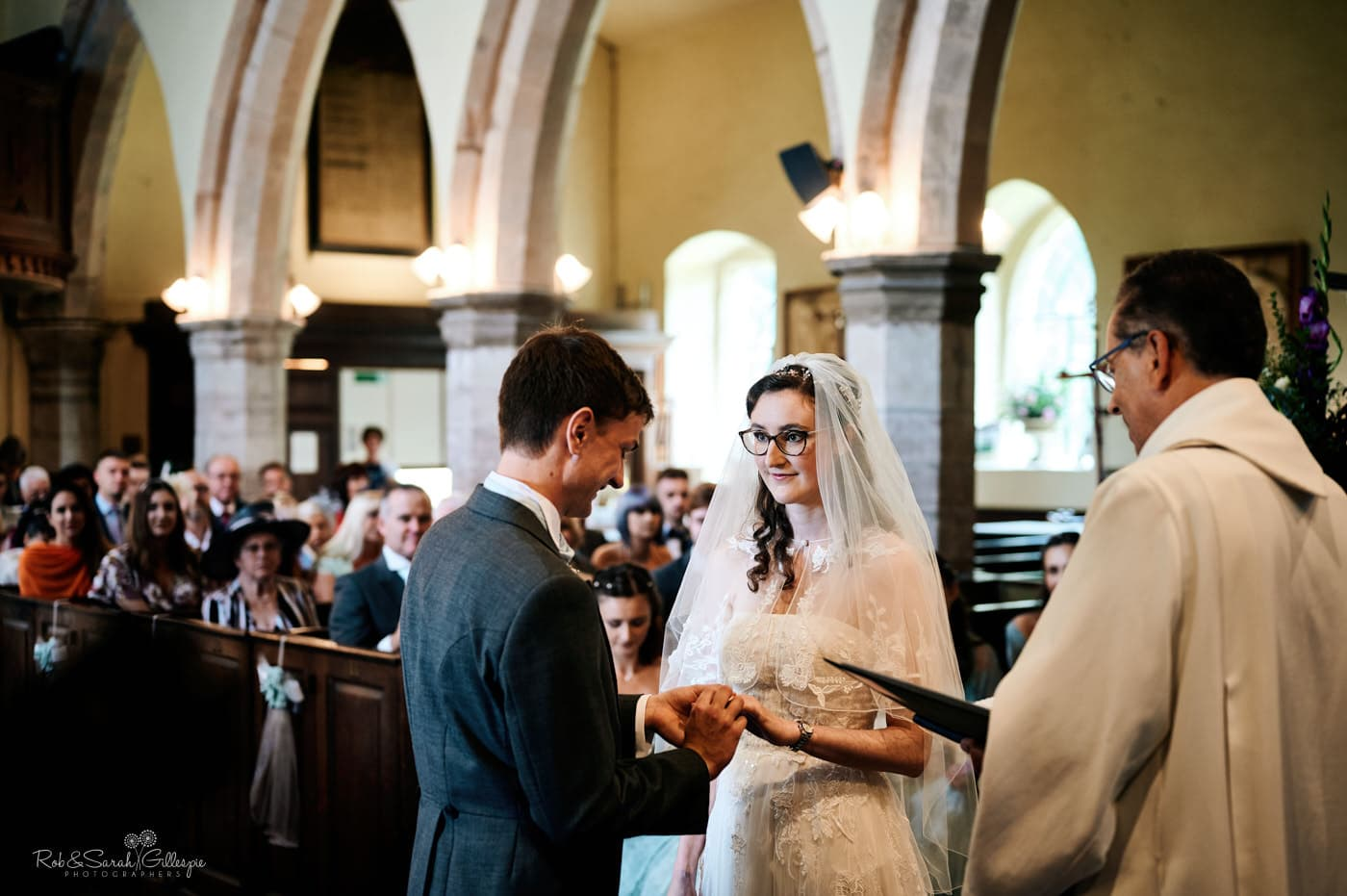 Bride and groom exchange wedding rings at Hanbury Church in Worcestershire