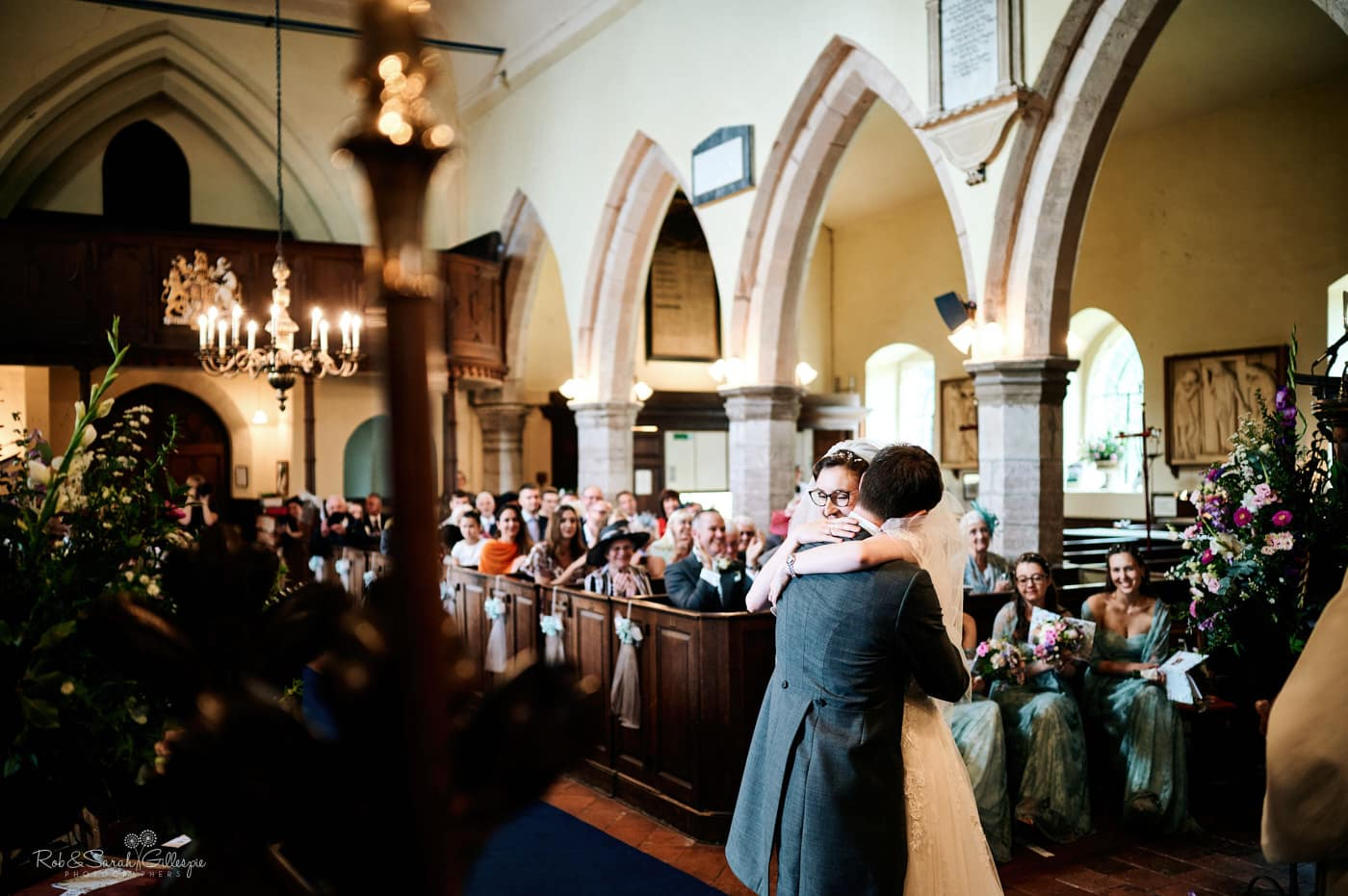 Bride and groom hug after getting married at Hanbury Church