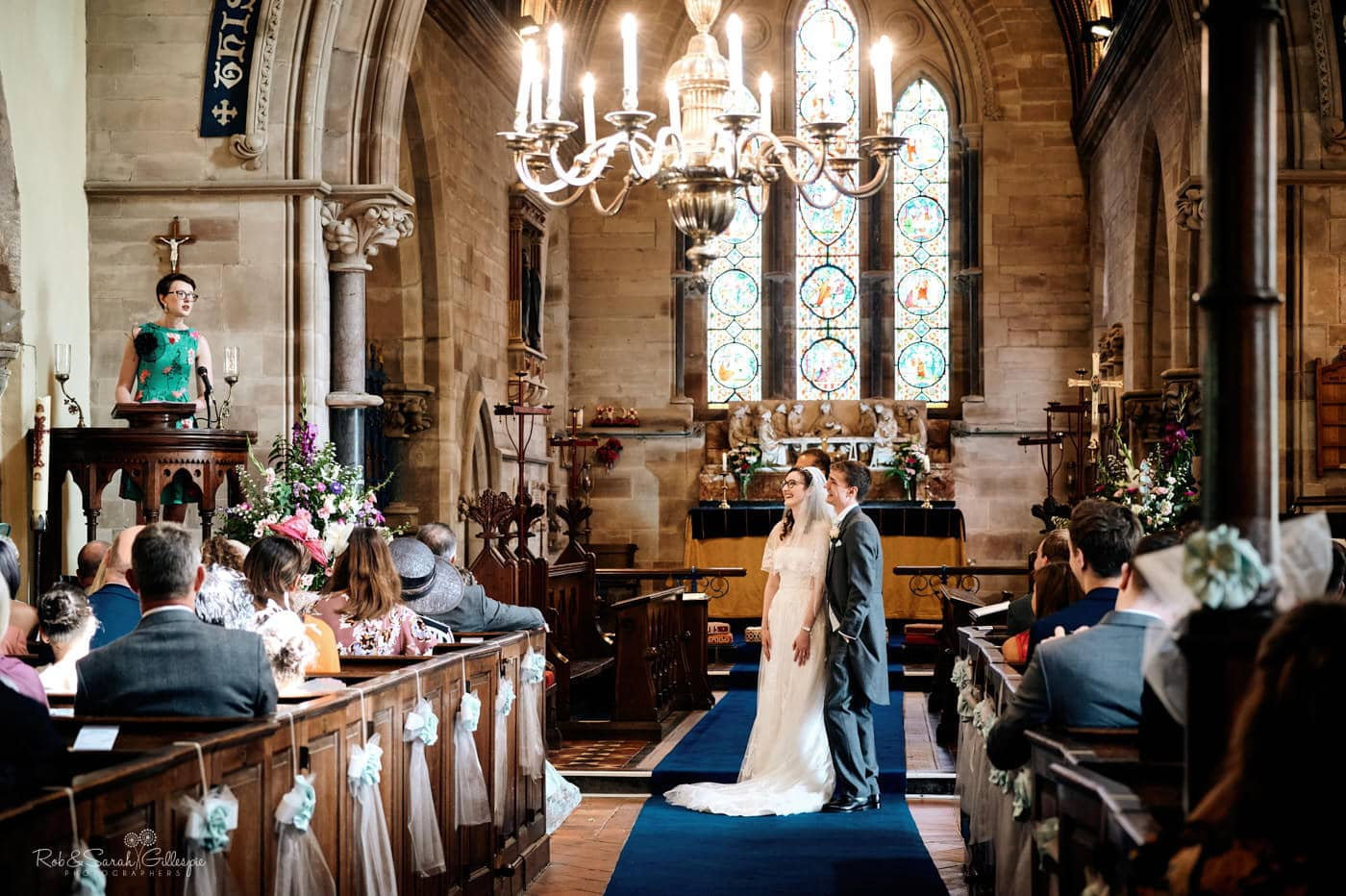 Bride and groom listen to guest reading during church wedding