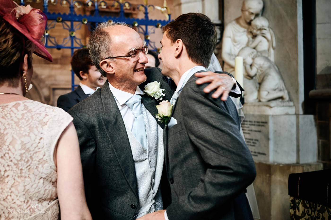 Groom's dad hugs son as they sign marriage register