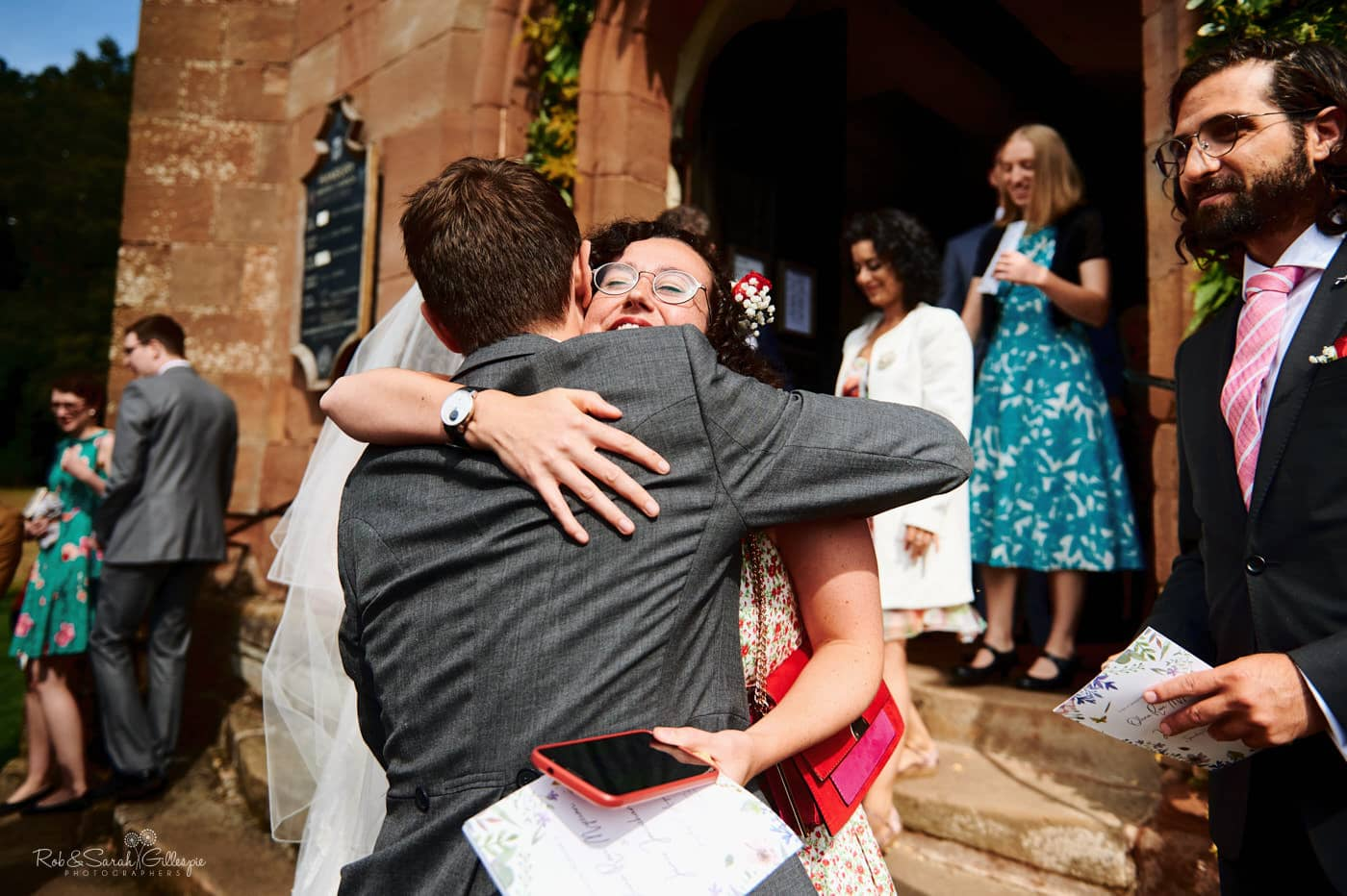 Weddings guests congratulate bride and groom after wedding service
