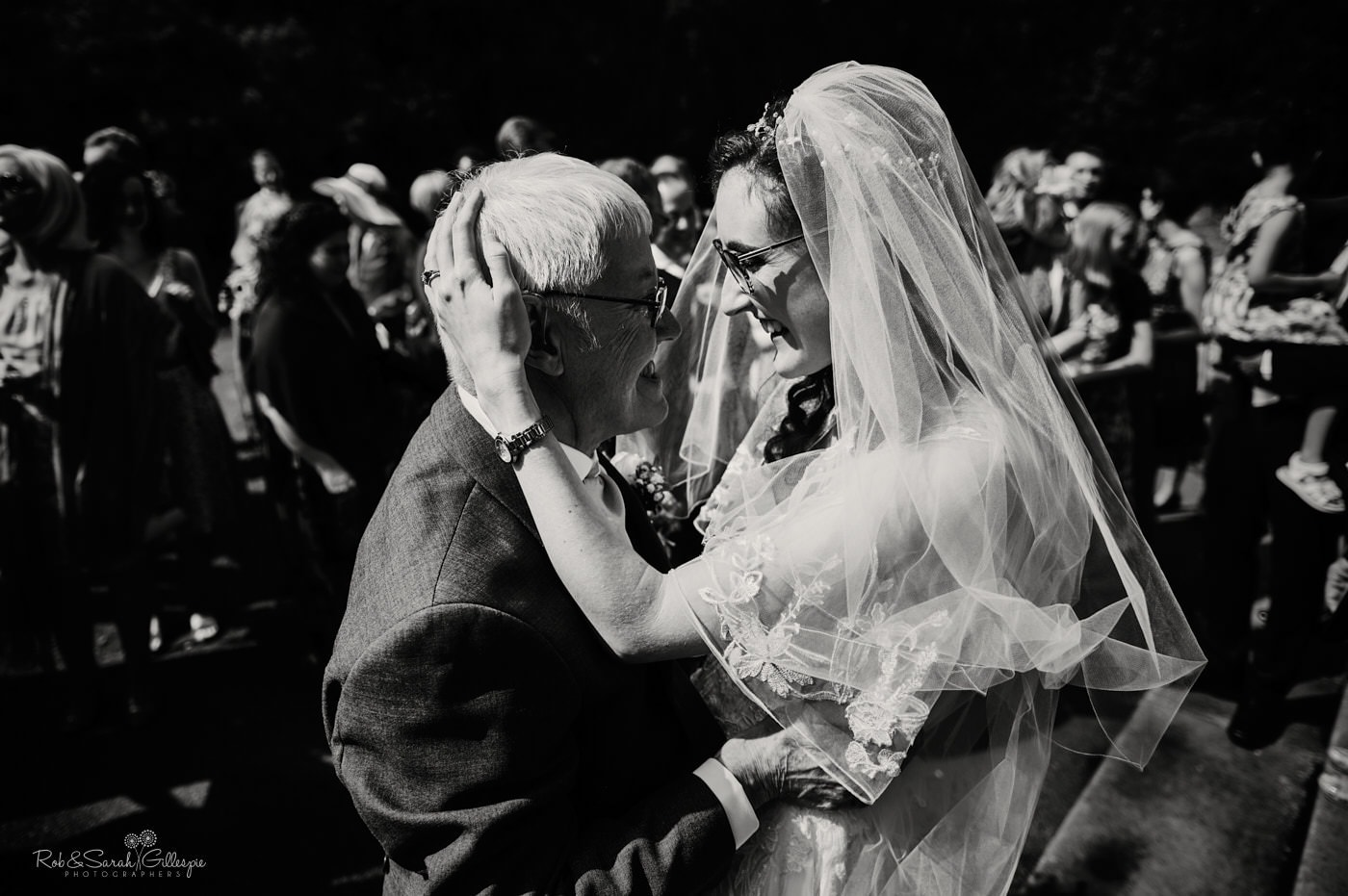 Bride hugs grandfather at Hanbury church wedding