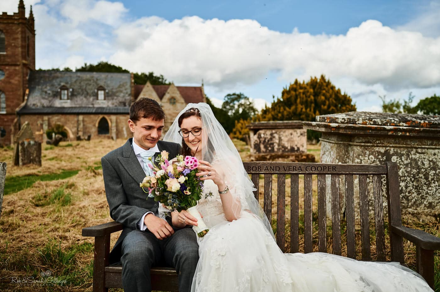 Bride and groom sitting on bench at Hanbury Church