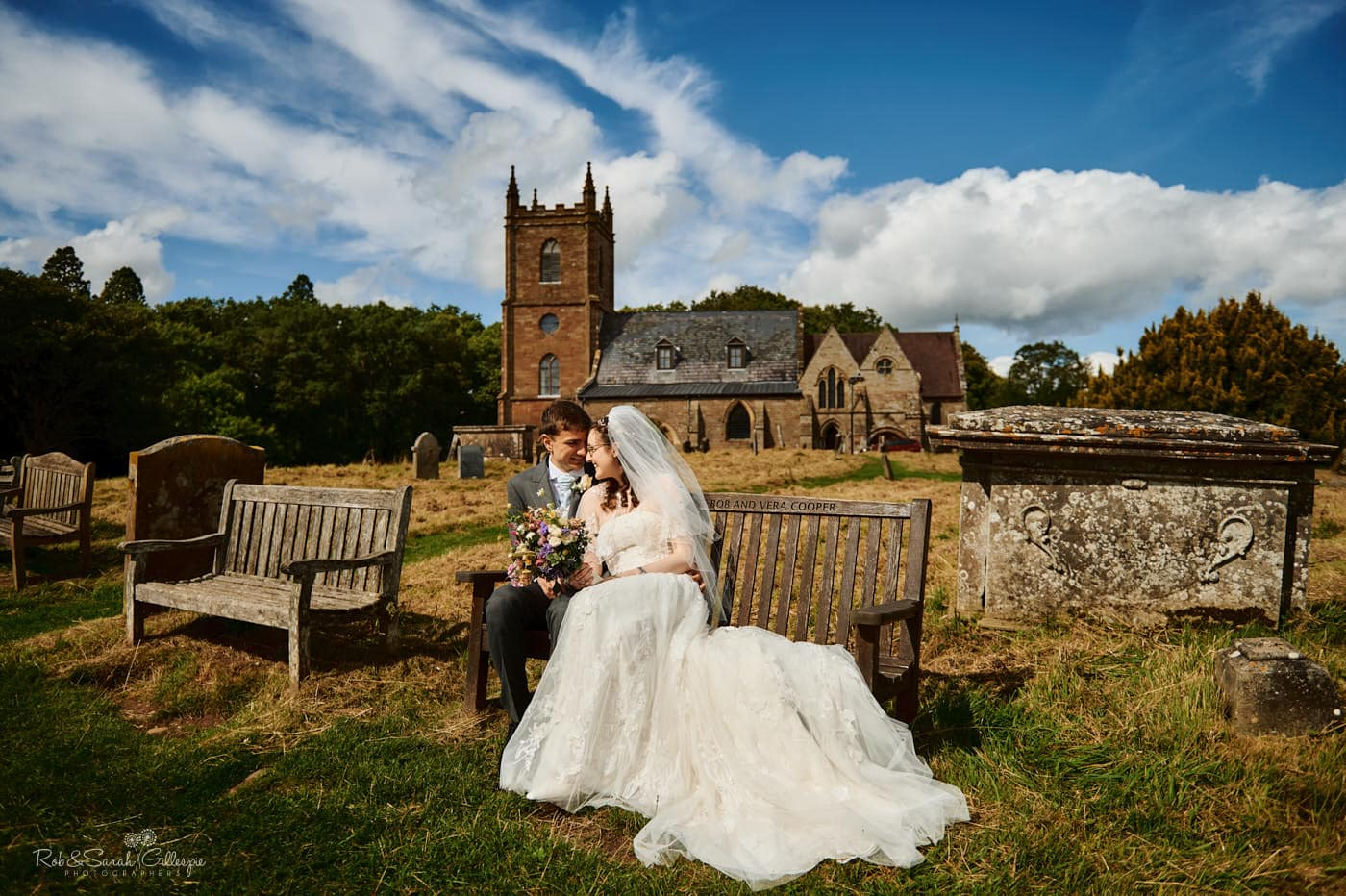 Newly married couple on bench at Hanbury church with beautiful weather