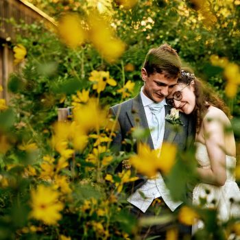Bride and groom at Avoncroft Museum with yellow flowers