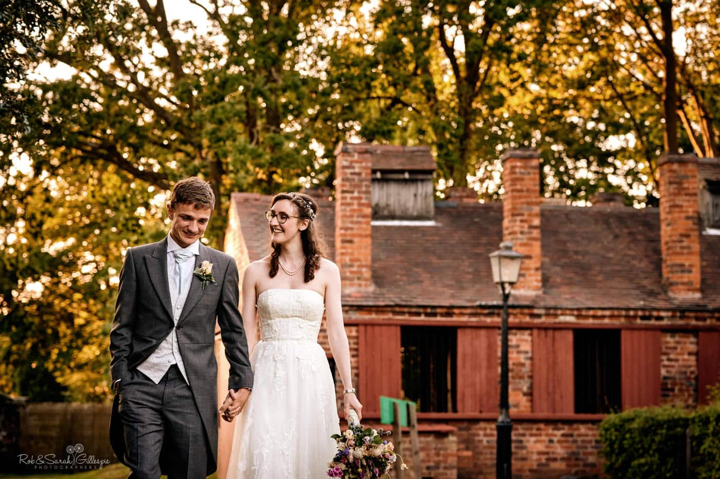 Bride and groom waking through Avoncroft Museum with old buildings and trees