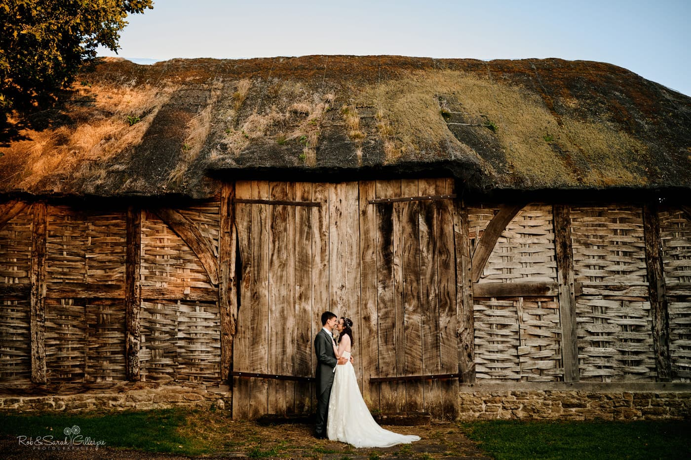 Bride and groom in front of old barn at Avoncroft Museum wedding