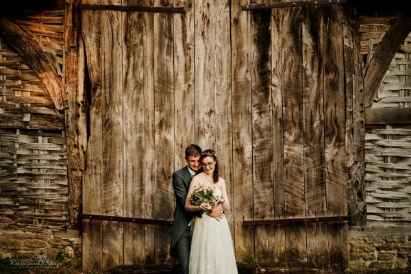 Bride and groom near old barn at Avoncroft