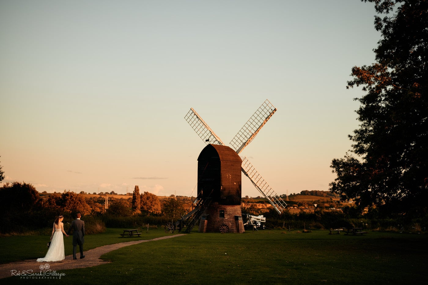 Bride and groom waking to windmill at Avoncroft Museum wedding in beautiful evening light