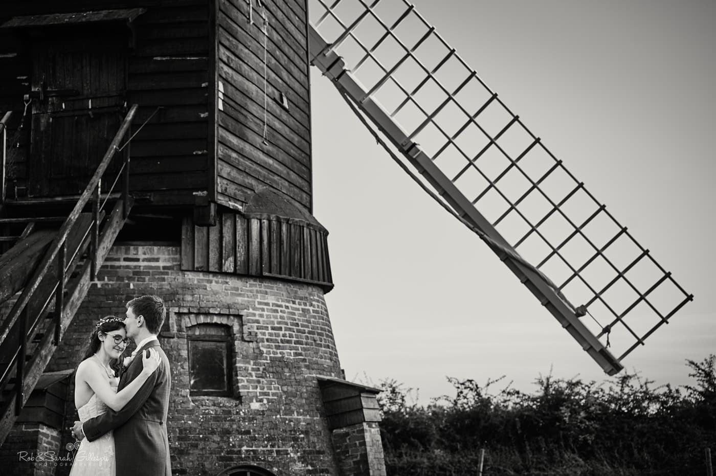 Newly married couple standing next to old windmill at Avoncroft Museum wedding
