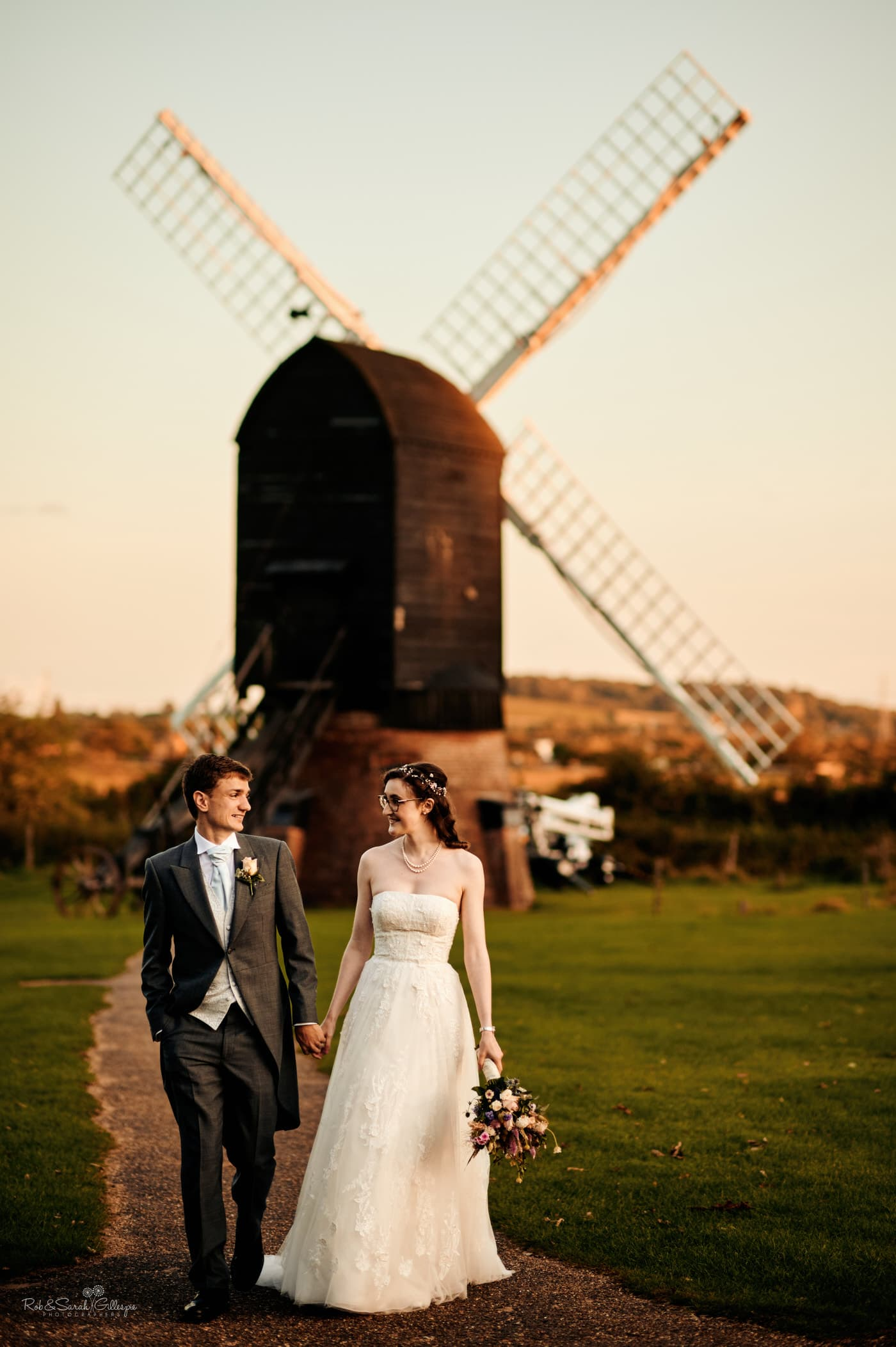 Bride and groom at Avoncroft Museum wedding, with old windmill in background