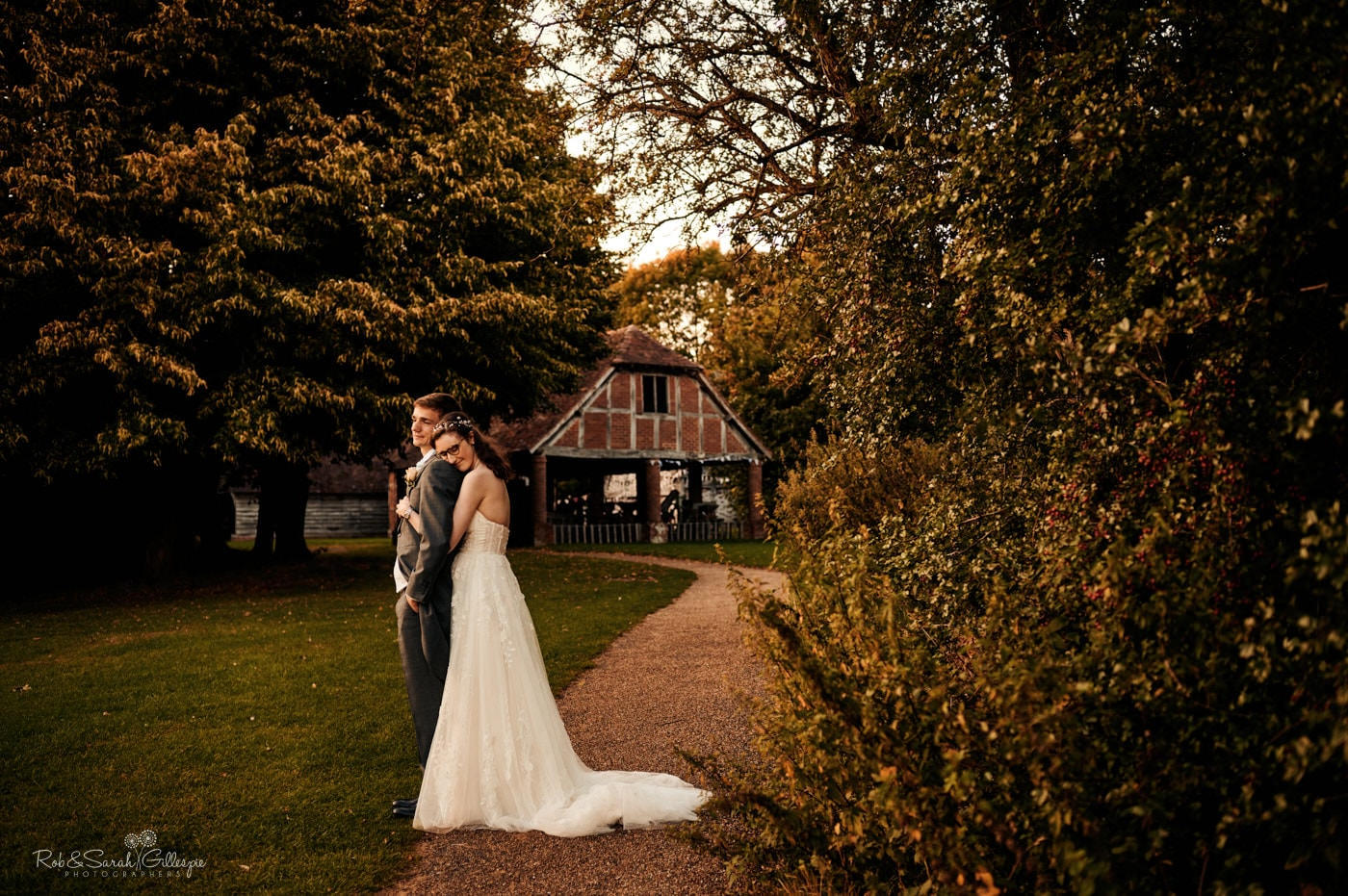 Happy bride and groom cuddling in front of old barn at Avoncroft Museum wedding