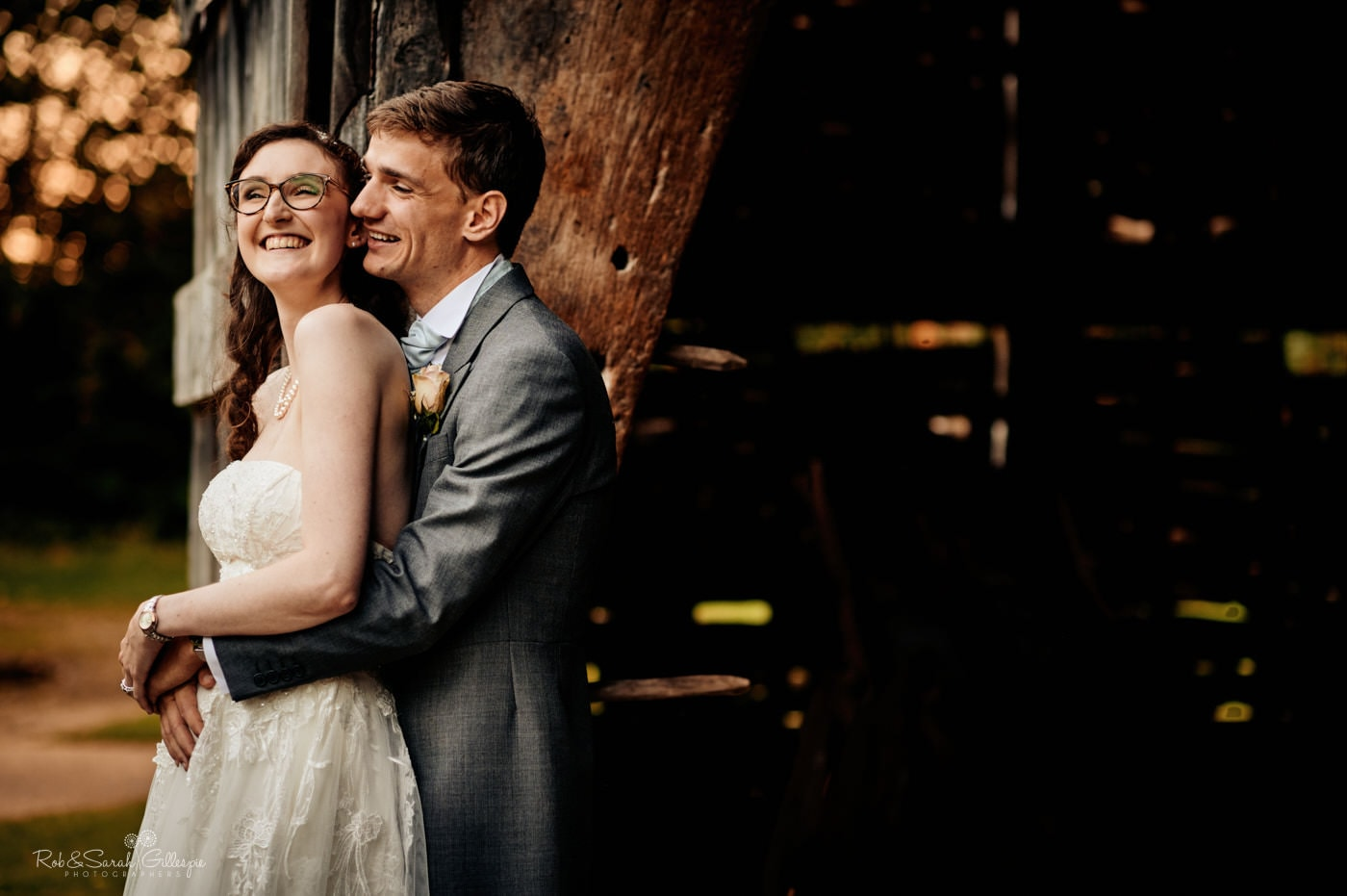 Happy bride and groom cuddling in old barn. Avoncroft Museum wedding photographers