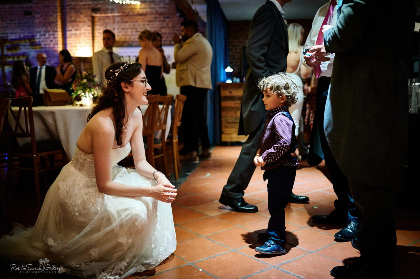 Bride talks to young boy at wedding reception