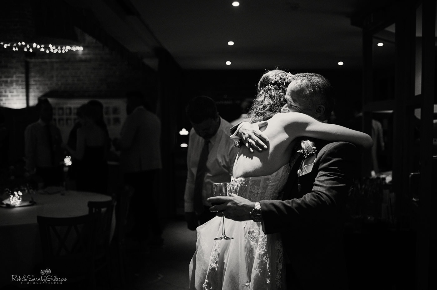 Bride hugs dad at evening wedding reception
