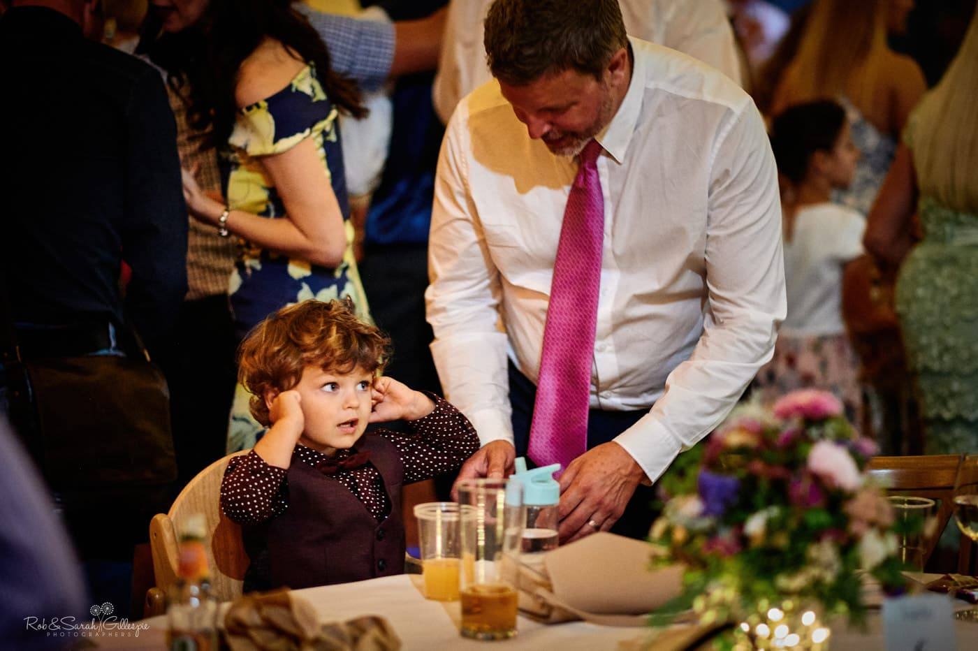 Young boy puts fingers in ears during evening wedding reception