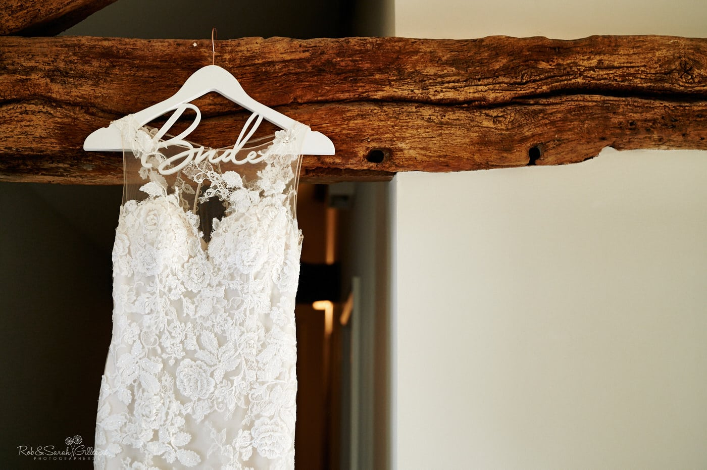 Wedding dress hanging from wooden beam