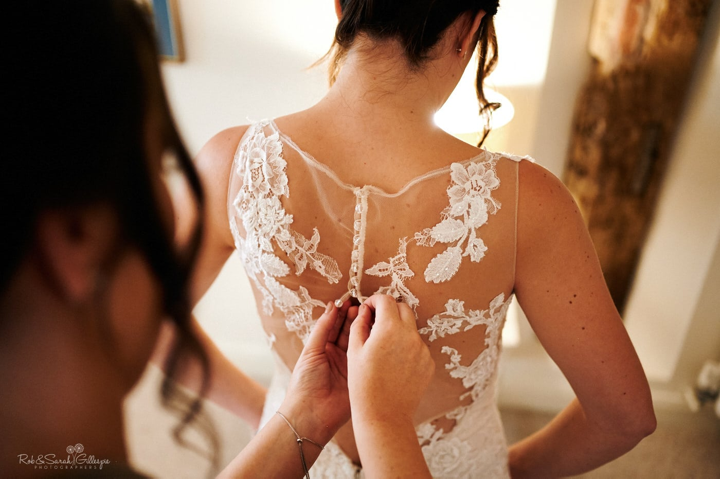 Bride has back of wedding dress fastened