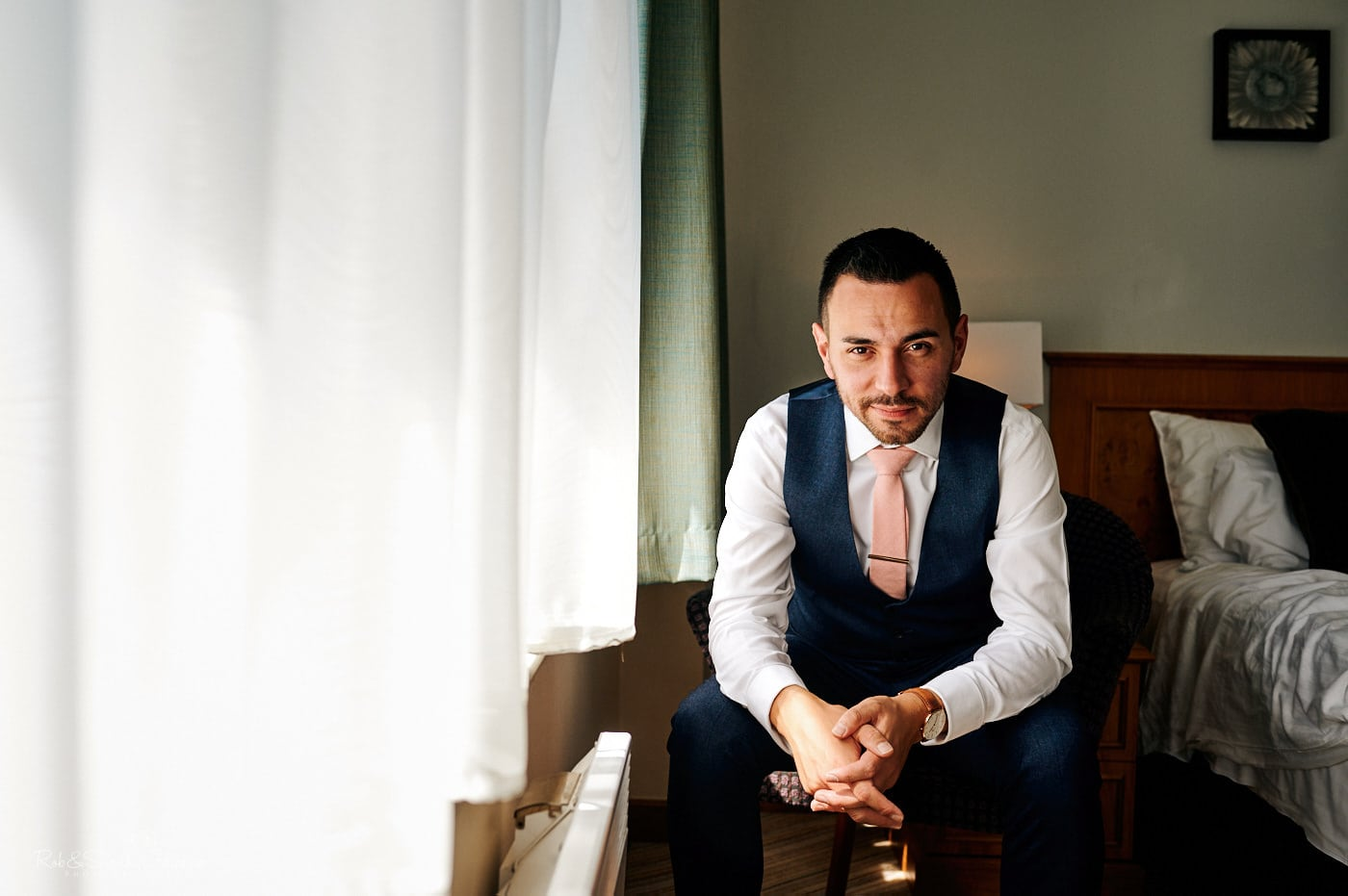 Portrait of groom sitting in hotel chair