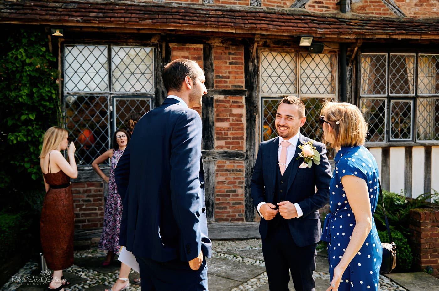 Groom greets wedding guests as they arrive