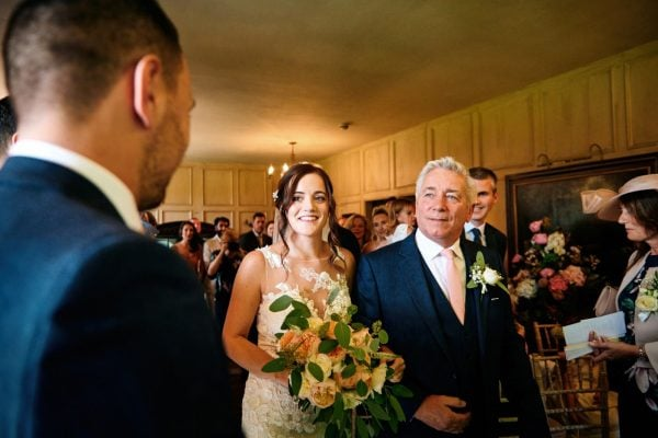 Bride and father walk up aisle during wedding ceremony