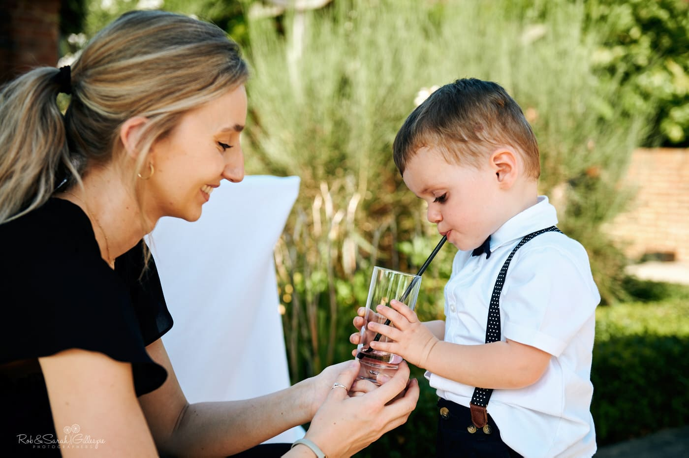 Female member of staff gives young boy drink on hot wedding day