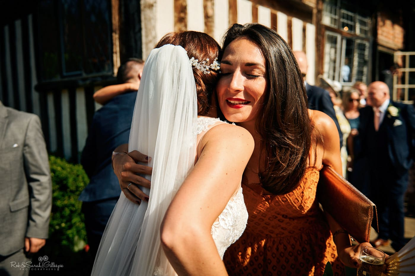 Wedding guest hugs bride after ceremony at Gorcott Hall