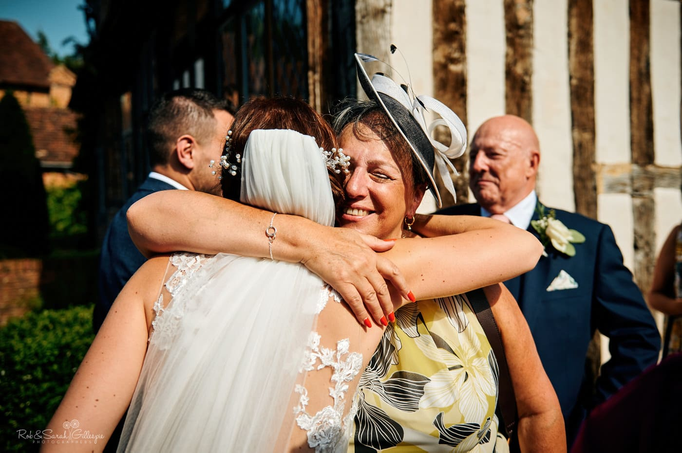 Bride hugged by guest at wedding