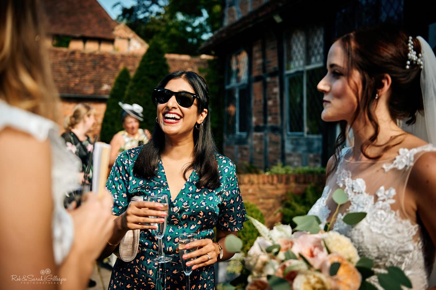 Wedding guests chat to bride during drinks reception